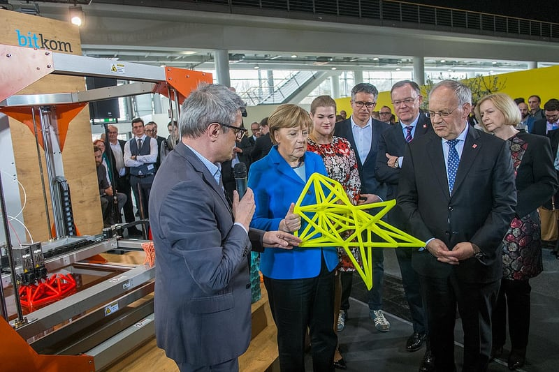 German Chancellor Angela Merkel standing near the BigRep ONE with a 3D printed stool