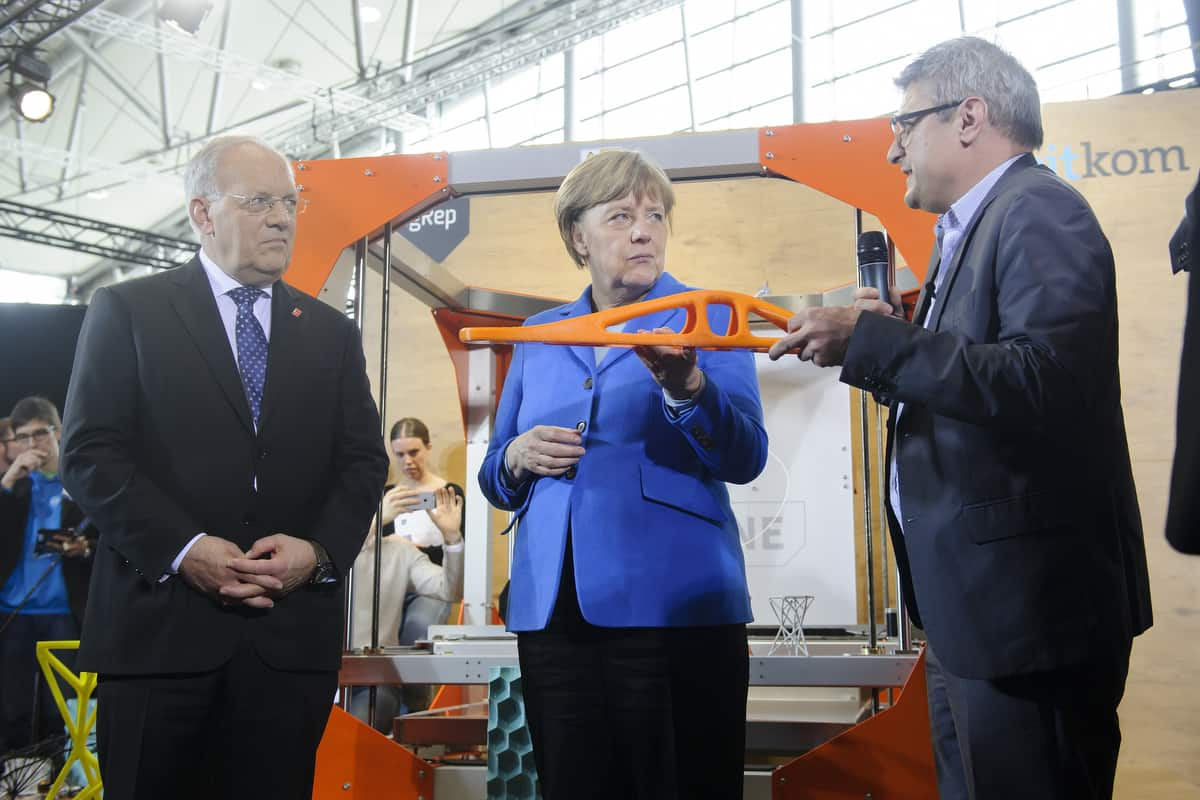 Angela Merkel with a 3D printed part and René Gurka